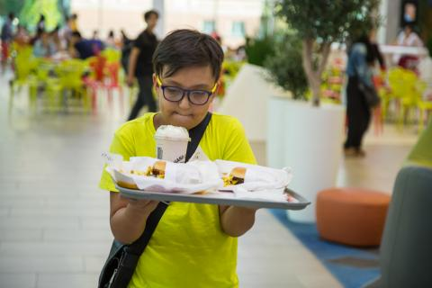 Yerzhan, 10, is carrying two burgers with fries and a milkshake