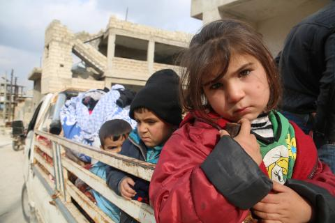 Children ride in the back of a truck as families flee from Idlib