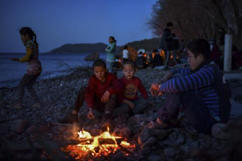 Children warm themselves around a makeshift fire on a beach, after arriving on the Greek island by inflatable dinghies, on March 2, 2020.