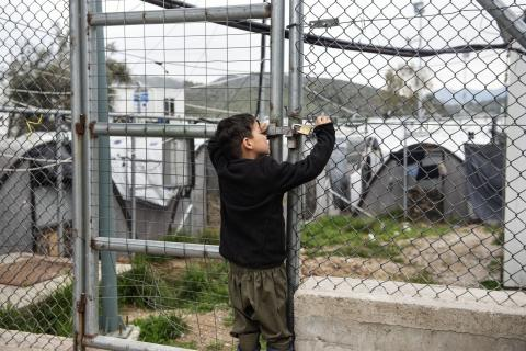 On 7 March 2020, a boy inspects the lock on a gate in the Reception and Identification Centre in Moria, on the island of Lesvos, in Greece.