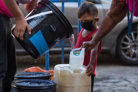 A child wearing a face mask due to the COVID-19 pandemic watches water being poured into a container in Caracas.