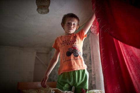 boy plays on his bed during a visit by social worker