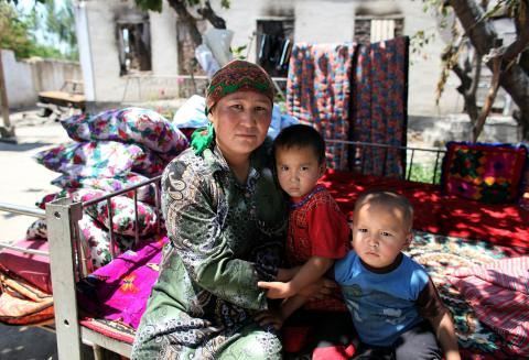 On 2 July 2010, Gulnara Kozybaeva sits with her daughter Akmaral, 4, and son Nurbek, 2, outside their burnt-out home in Furkat District, in the southern city of Osh. Their house was destroyed during riots in the recent conflict. Their large ethnic Kyrgyz family now shares a tent in the courtyard of their home.