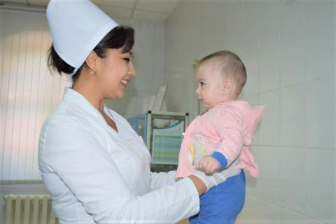 Nurse Aziza Abduazimova looking at baby Iymona.