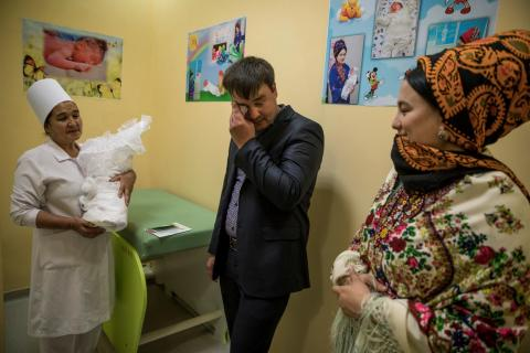 A new father in a maternity ward in Turkmenistan wipes away a tear as he prepares to leave the hospital with his new son.