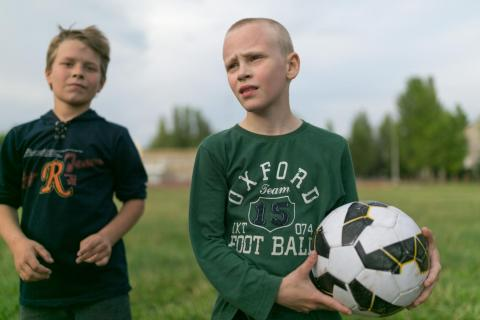 Dima, 14 years old, stands holding a football at the field where he plays with his friends in eastern Ukraine.