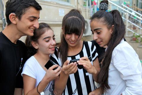Four teens huddle around a point-and-click camera.