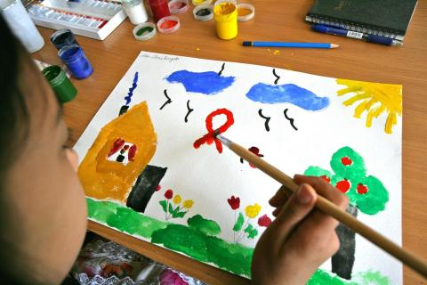 A child paints a scene showing a house with a HIV awareness ribbon in the sky.