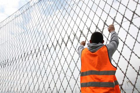 A 17-year-old boy hangs onto a fence at a detention centre where he has spent the last 19 months. He is only half way through his sentence.