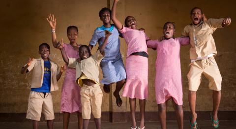 A group of children jump in the air with smiles on their faces in a classroom in Guinea.