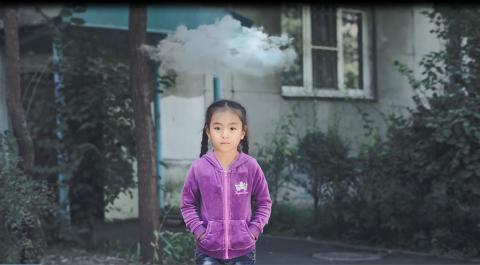 A girl standing with a cloud above her head.