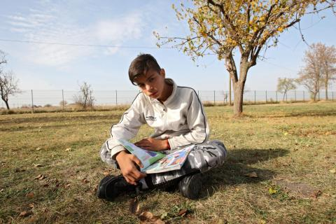 Mohamed siting outside with the book he took on his journey form Afghanistan.