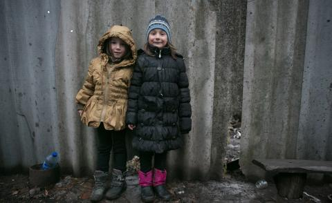 Sisters Sofia, 6, (left) and Karina, 7, stand near a fence of their house in Olenivka settlement in the non-government controlled part of Donetsk region.