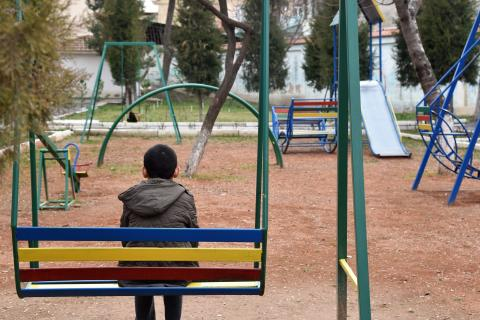 Timur sits on a swing in the yard of the Center for Social and Legal Aid to Minors in Uzbekistan's capital city Tashkent.