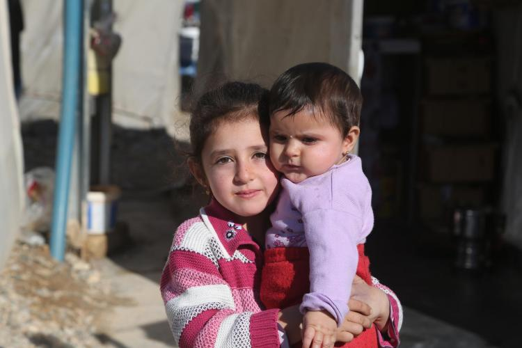 Girl holding her baby brother at a refugee center in Turkey.