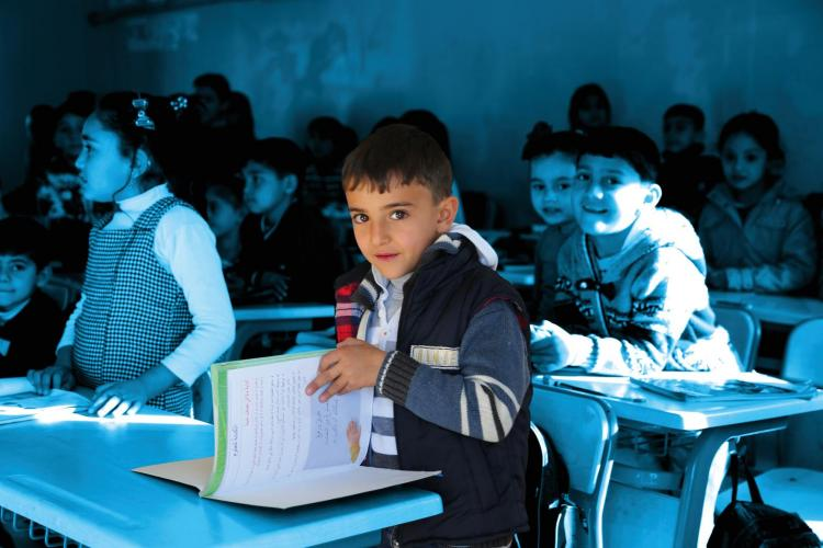 Elias, 7, prepares to read for the class at his school in Suruc Refugee Camp, Turkey.