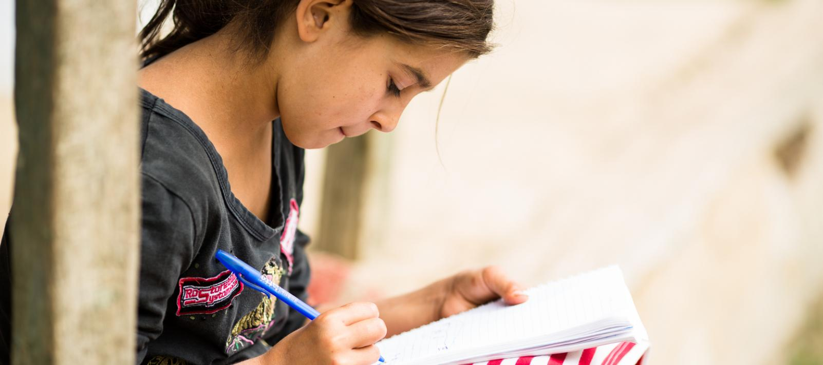Loredana, 11 years old, sits doing her homework on her porch at her home in Romania.