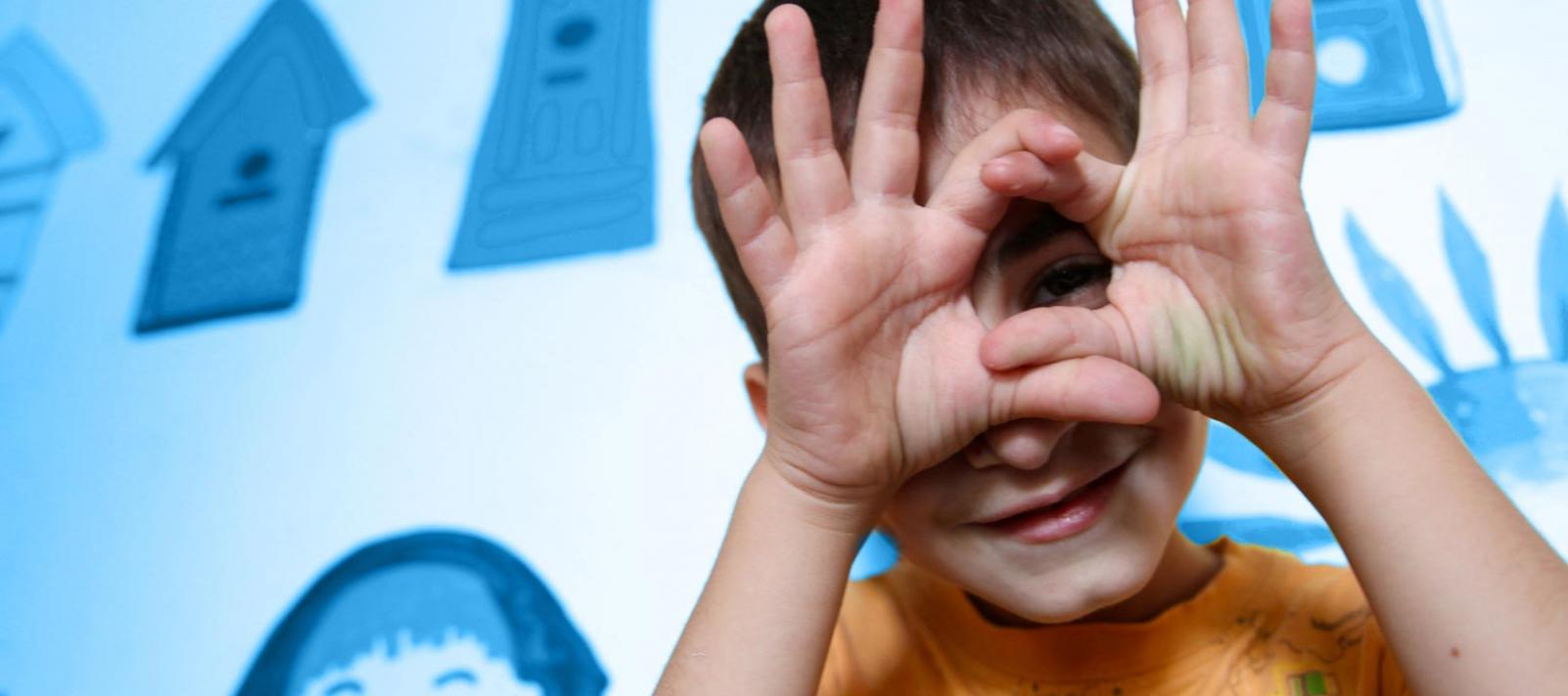 A child peers through his fingers towards the camera