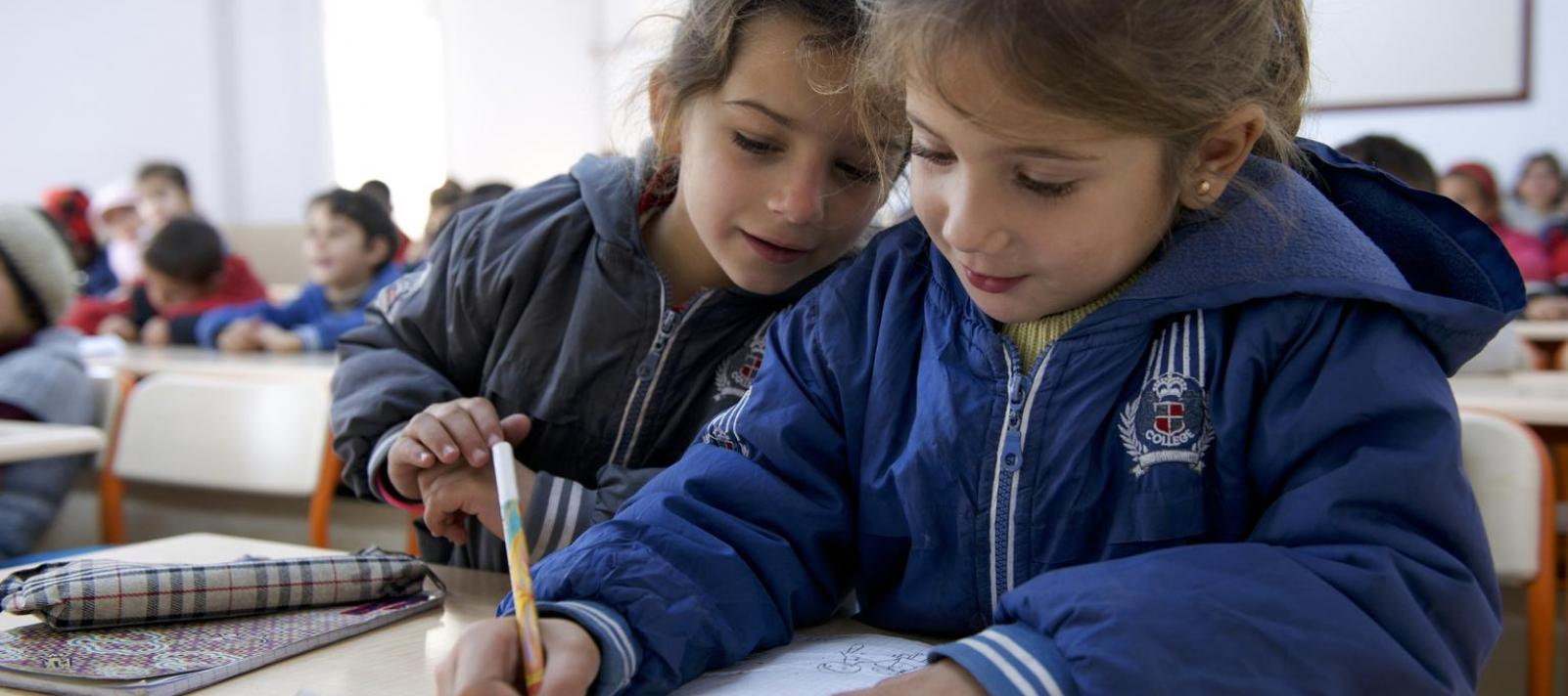In Turkey, a girl looks over the shoulder of another girl, who is drawing, in their Grade 1 class at a UNICEF-supported school.
