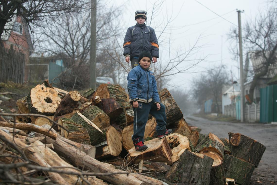 Vitia and Vania play war on a pile of wood not far from Vania's house in Avdiivka, Donetsk region.