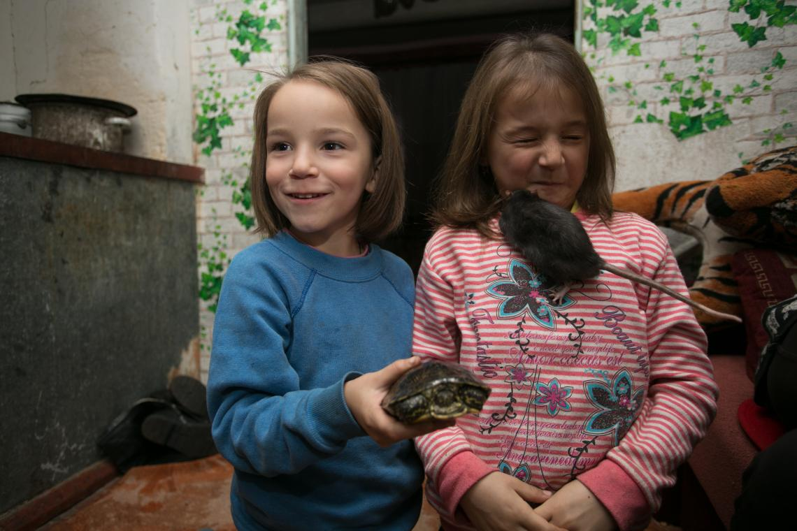 Sisters Sofia and Karina play with their pet tortoise and rat in their house.