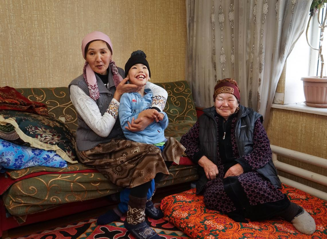 Adilet smiling next to his mother Nazira and grandmother Bubugul.