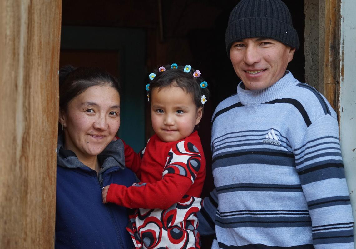 Begayim holds her daughter Latifa next to husband Myktybek as they smile for the camera.