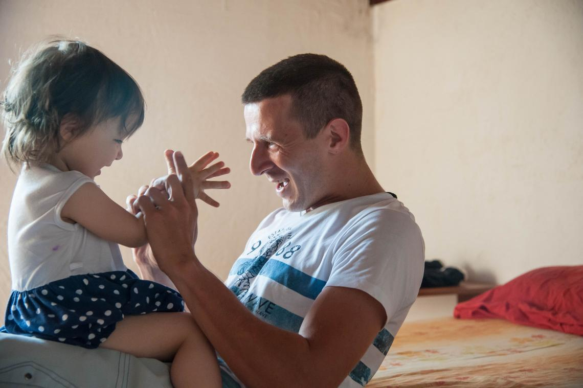 A father plays with his daughter Iris at their home in Serbia.