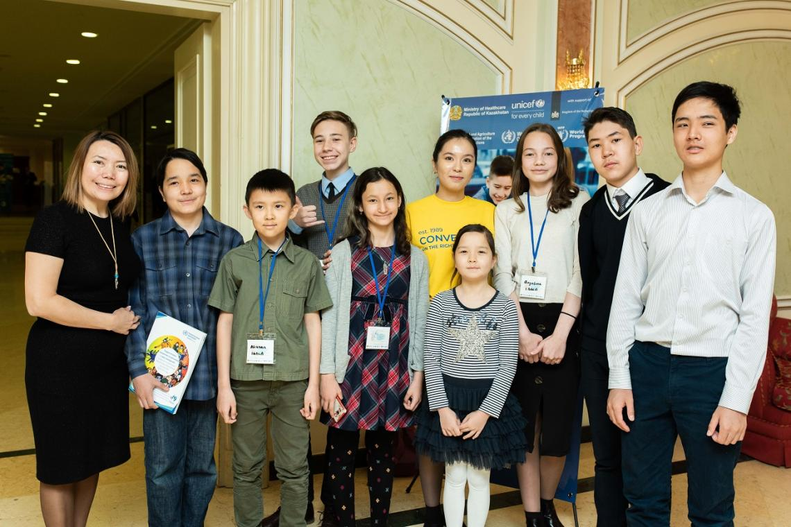Youth participants at the regional symposium on nutrition in Kazakhstan pose for a photo with UNICEF National Ambassador Dinara Saduakassova.