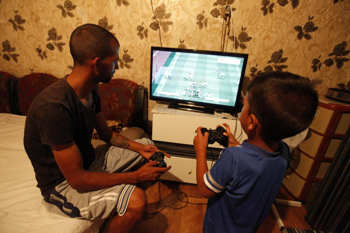 A father from vulnerable community plays a video game with his young son.