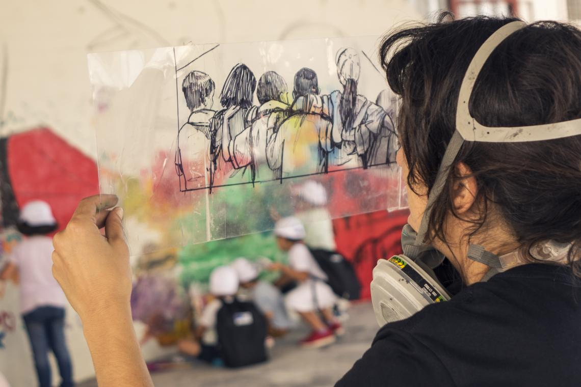 Artist Alice Pasquini designing a wall mural during a day-long event organized by UNICEF at Skaramagkas refugee camp in Athens, Greece.