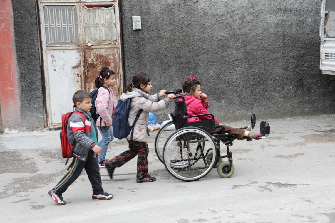 Emine being pushed in her wheelchair by her siblings.