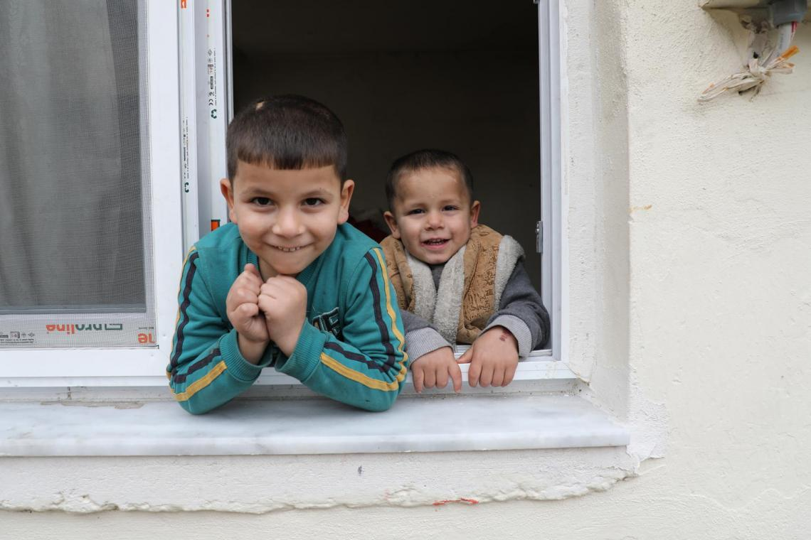 Two of Emine's younger brothers lean out of a window for the camera at their home in Adana.