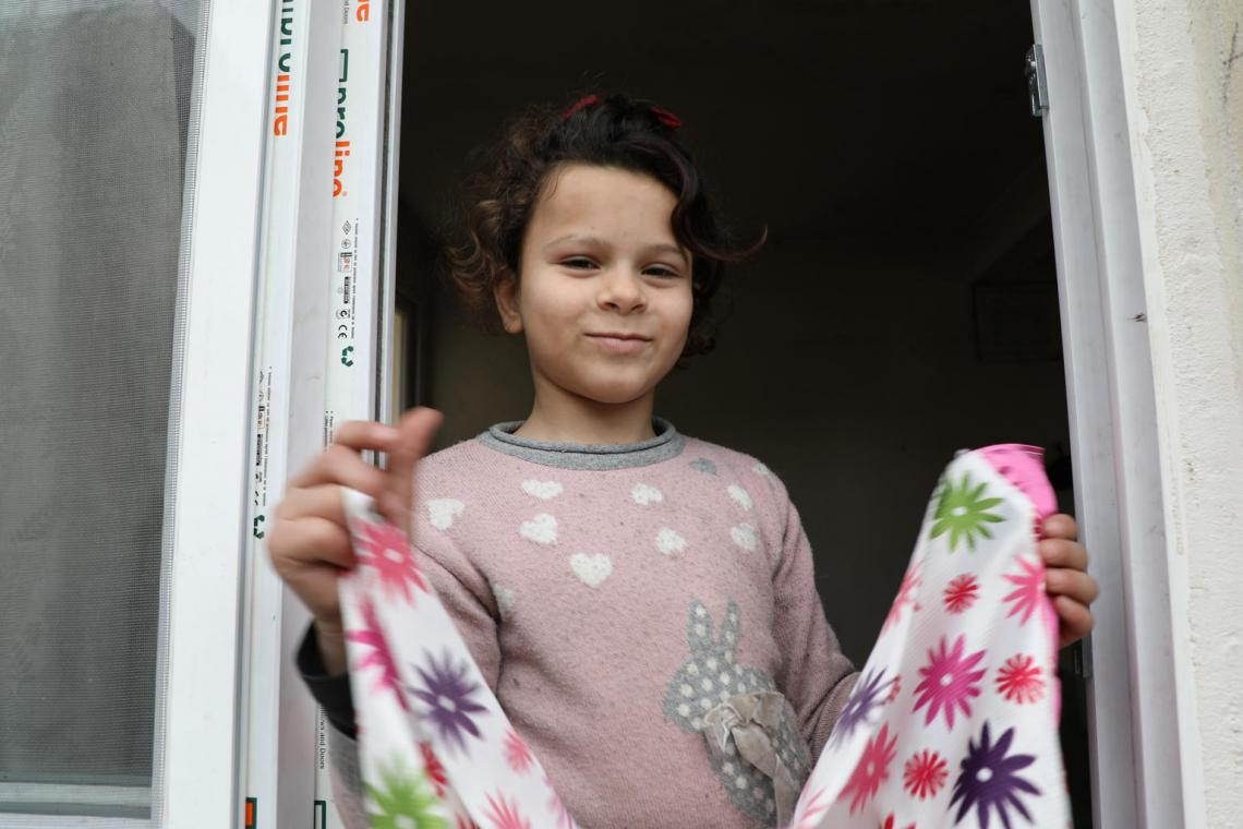 Emine grins as she folds a sheet at their home in Adana.
