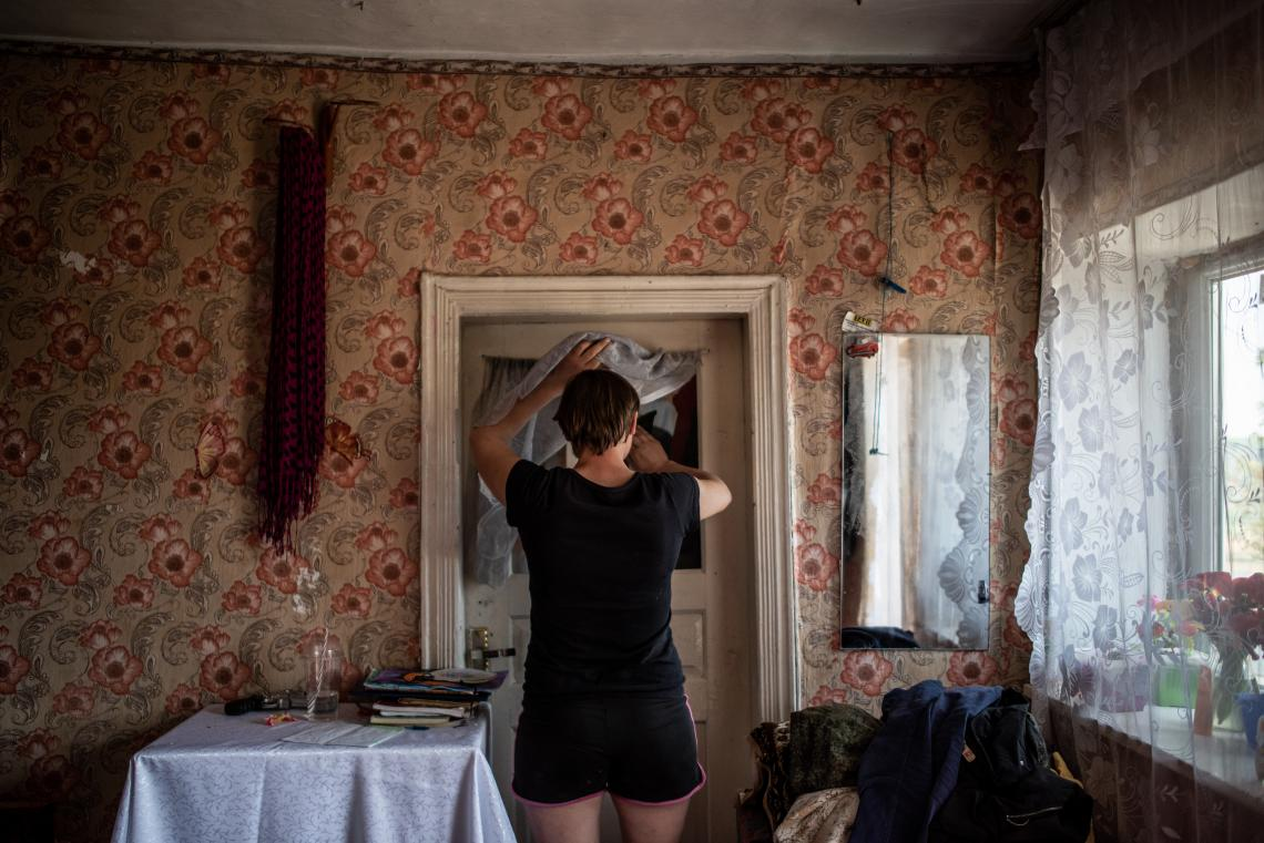 Silvia cleans a window at her small home in Moldova.