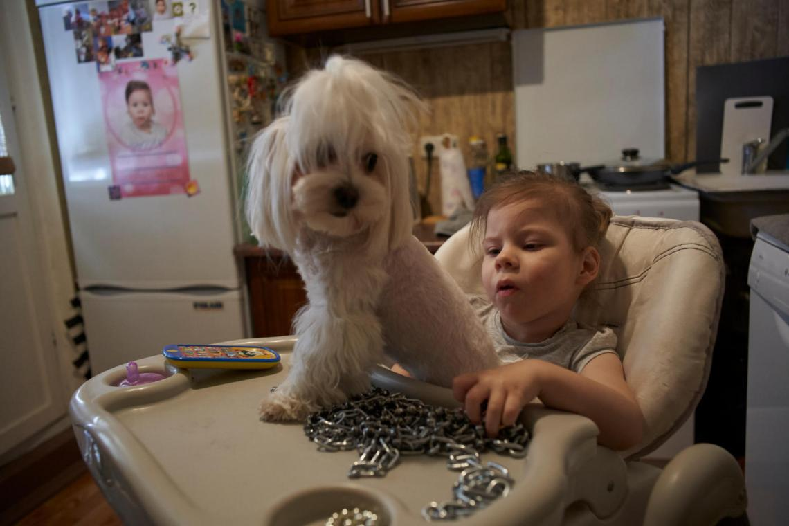 Three-year-old Agatha, in a high chair with her dog, plays with a shiny chain at home in Minsk, Belarus.