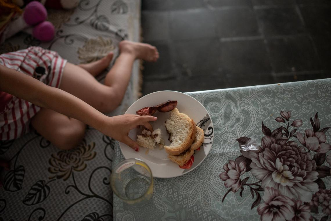 Fabliona, 4, reaches for her breakfast sandwich, in the apartment where she lives with her mother Jeta, in Tirana, Albania, on June 7, 2018.