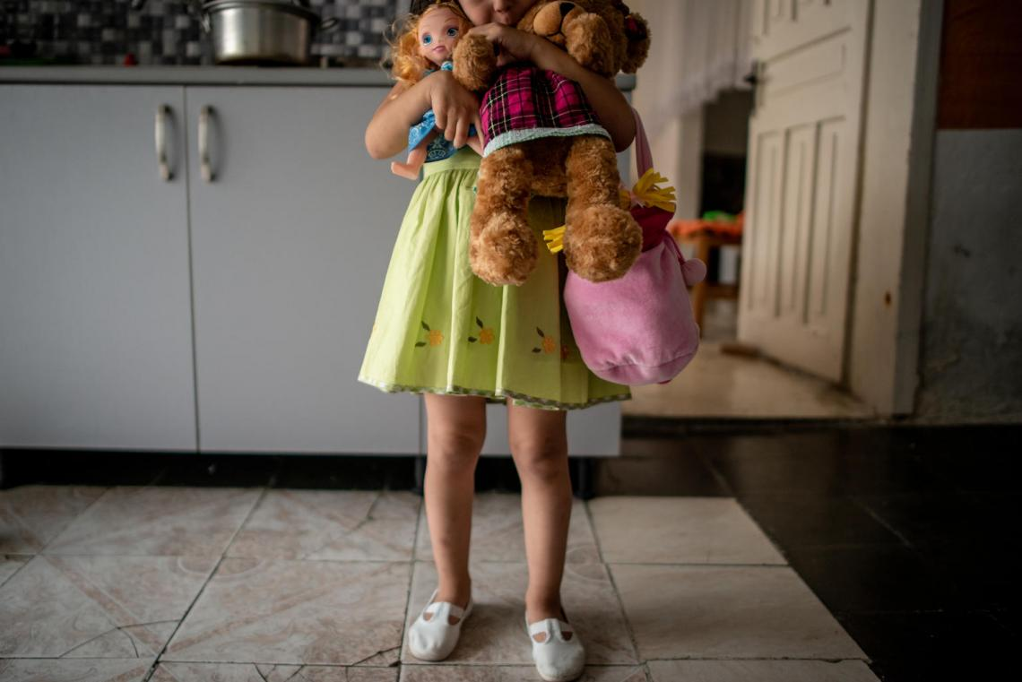 Fabliona, 4, holds her toys getting ready to go to a part with her mother Jeta, 24, in Tirana, Albania, on June 8, 2018.