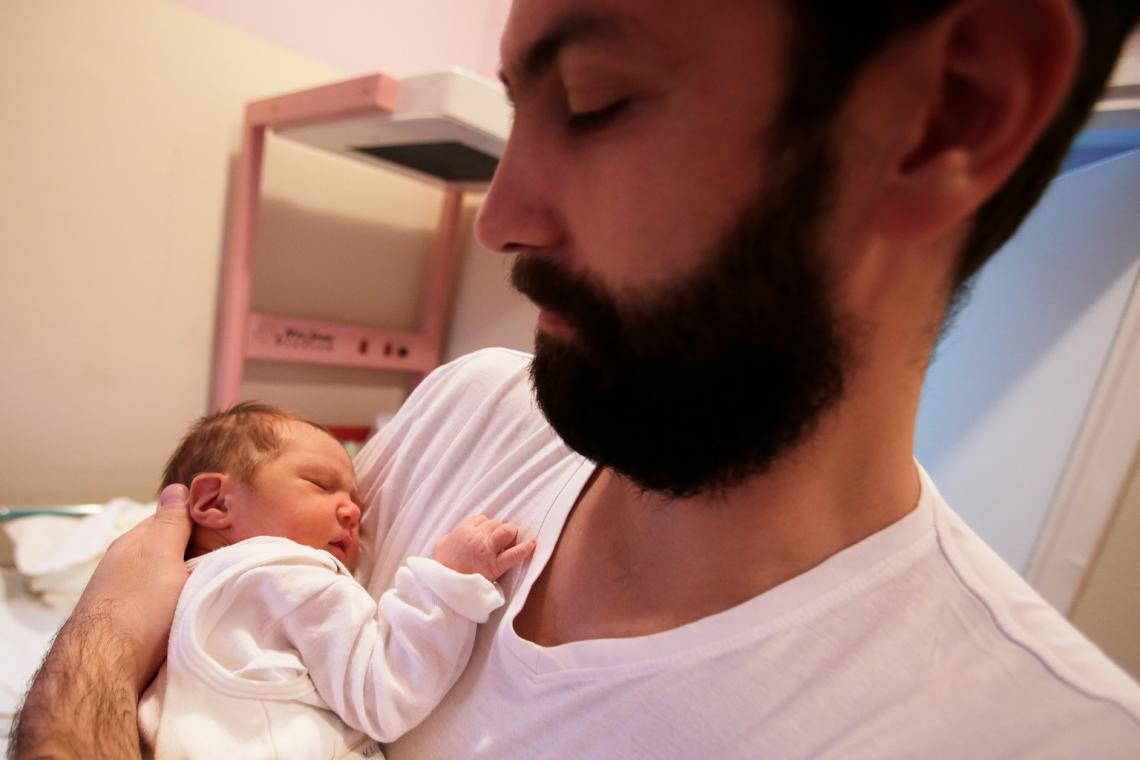 A father cradles his three-day-old baby in a hospital in Serbia.