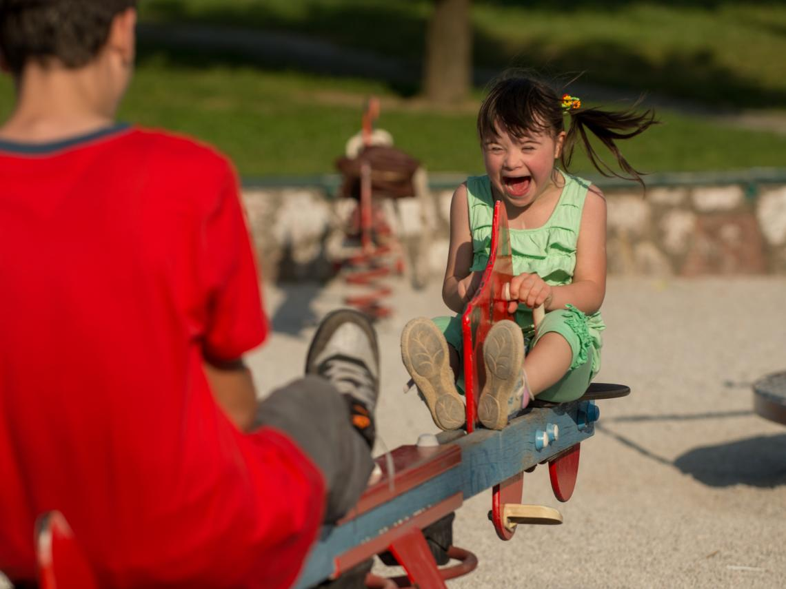 A girl with a disability plays on a see-saw in a park in Bosnia and Herzegovina.