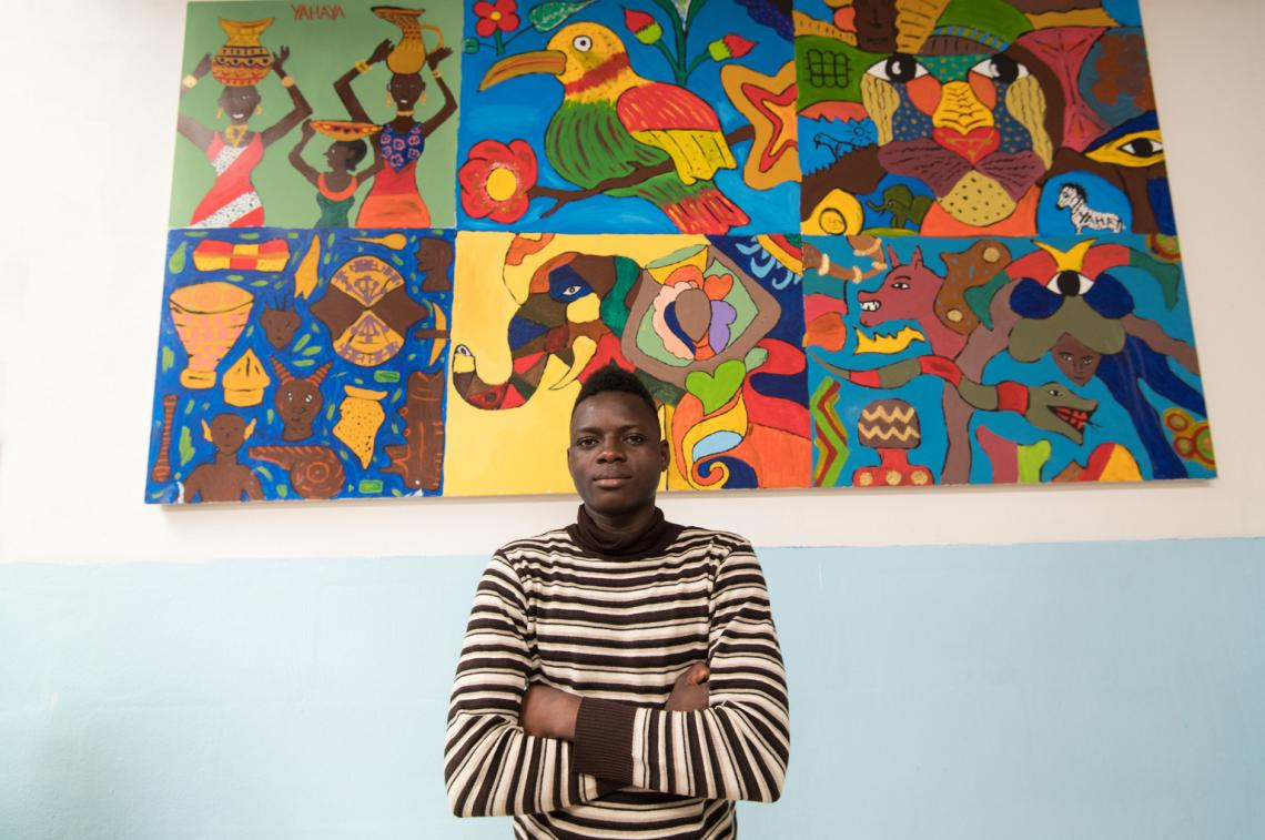 Yahya, aged 17, from Burkina Faso, poses in front of his painting.