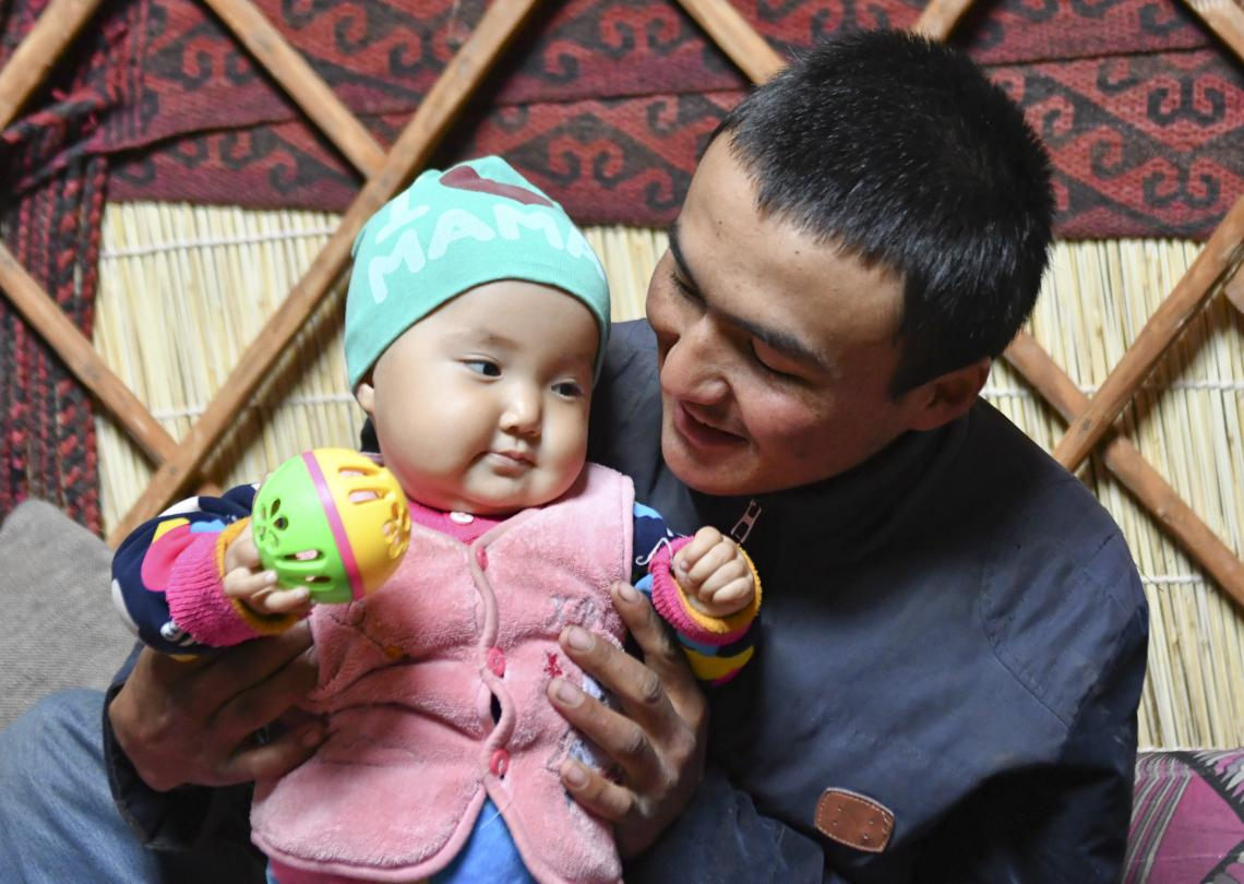 A father plays with his young daughter at their home in Kyrgyzstan.