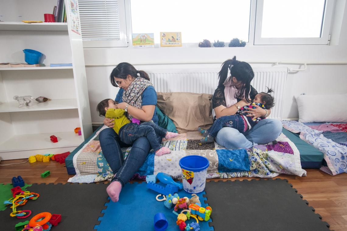 In a UNICEF-supported space for refugee and migrant families, two mothers breastfeed their babies.
