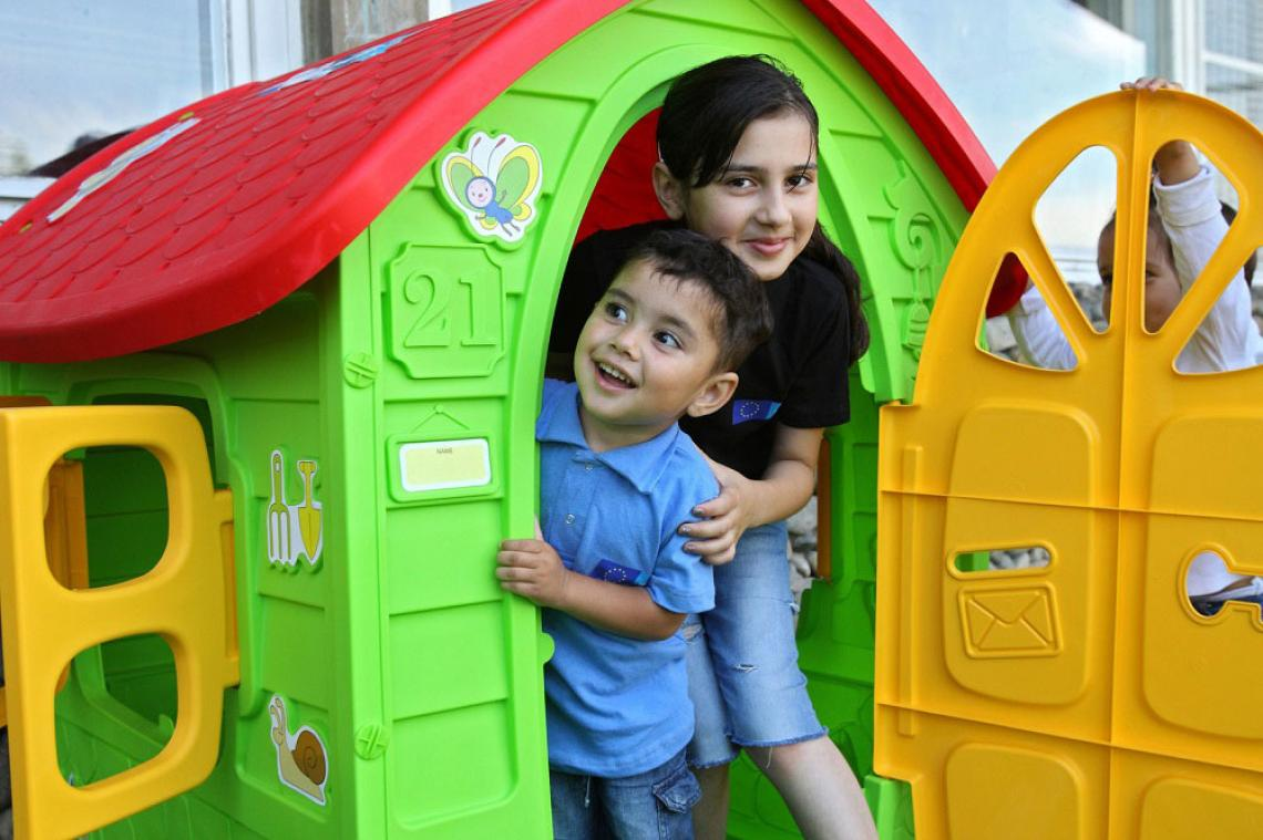A girl and a boy peek out of a playhouse door