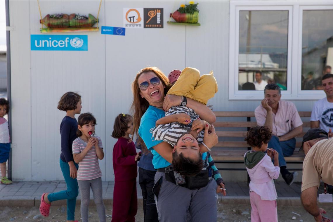 Children and UNICEF staff playing in a migrant reception centre in the former Yugoslav Republic of Macedonia