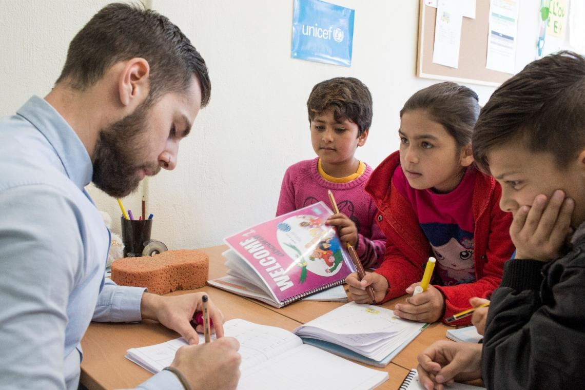 Refugee and migrant children and an educator at a UNICEF-supported education centre in Ioannina, Greece.