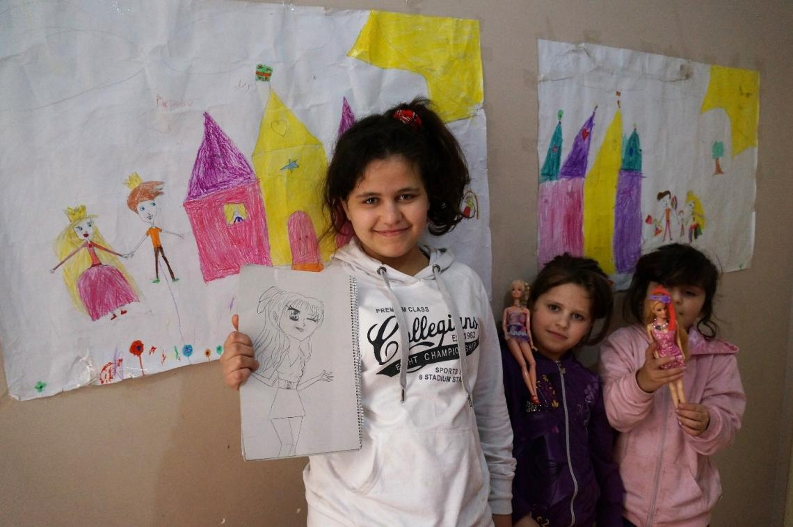 Sisters Nour 11, Rawan 8, Judy 7, show off their drawings in their new apartment  in Athens, Greece.
