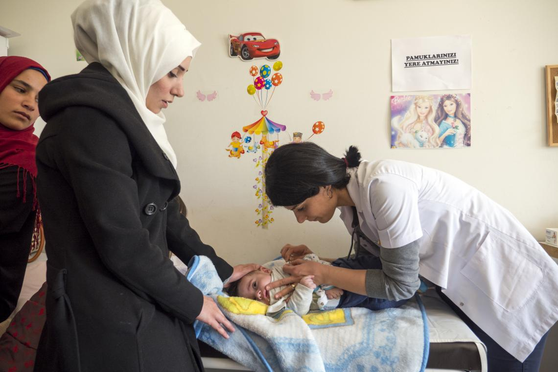 A health worker vaccinates a one-year-old Syrian refugee boy at a neighbourhood health centre in Gaziantep, Turkey.