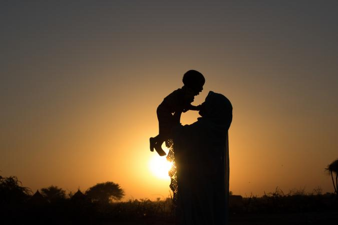 A silhouetted mother, who was married at 14, holds up her young child at sunset in a rural village in Chad.