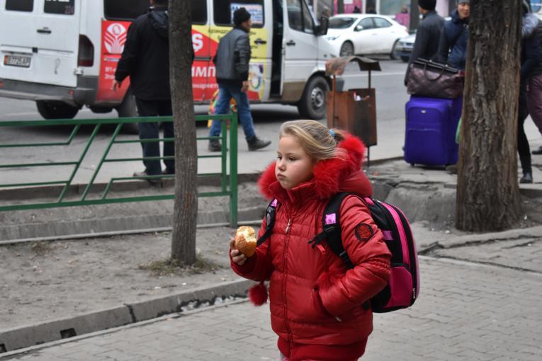 A girl in the capital city of Bishkek, Kyrgyzstan eats street food